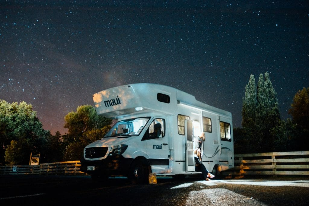 RV on the mountains under a beautiful night sky