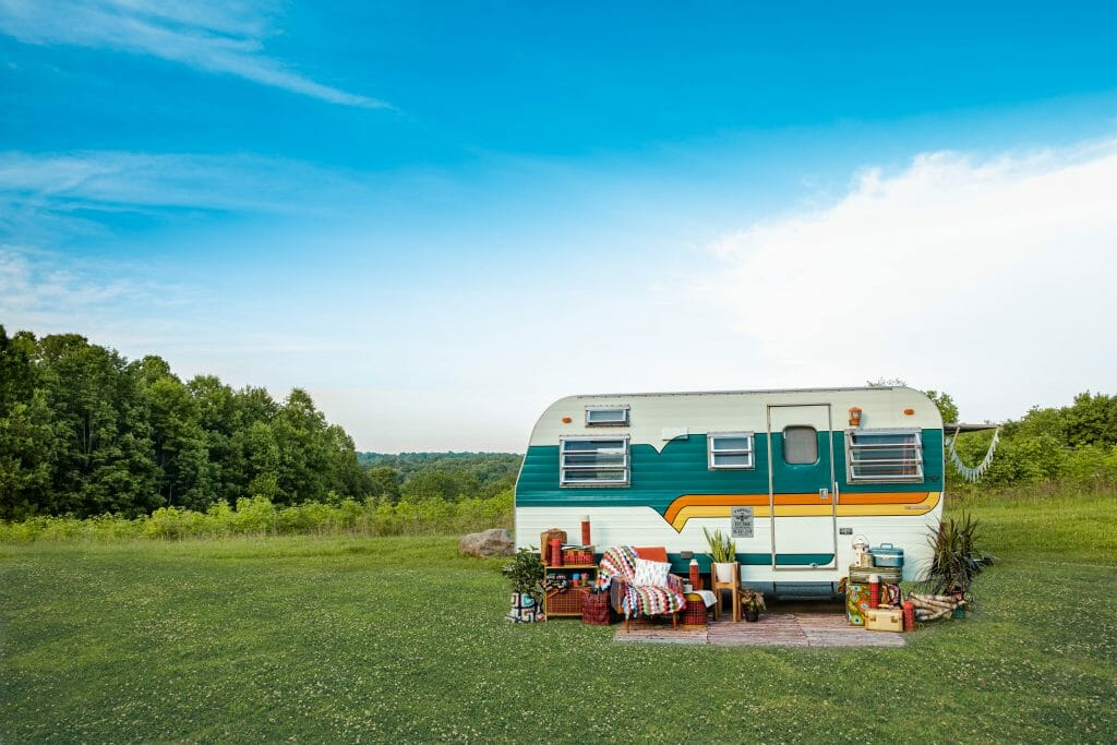 RV trailer out in the field with colorful furniture setup outside